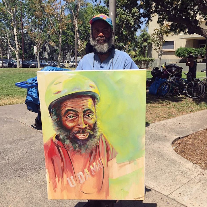 Homeless man Daryl holding the portrait Peterson painted of him
